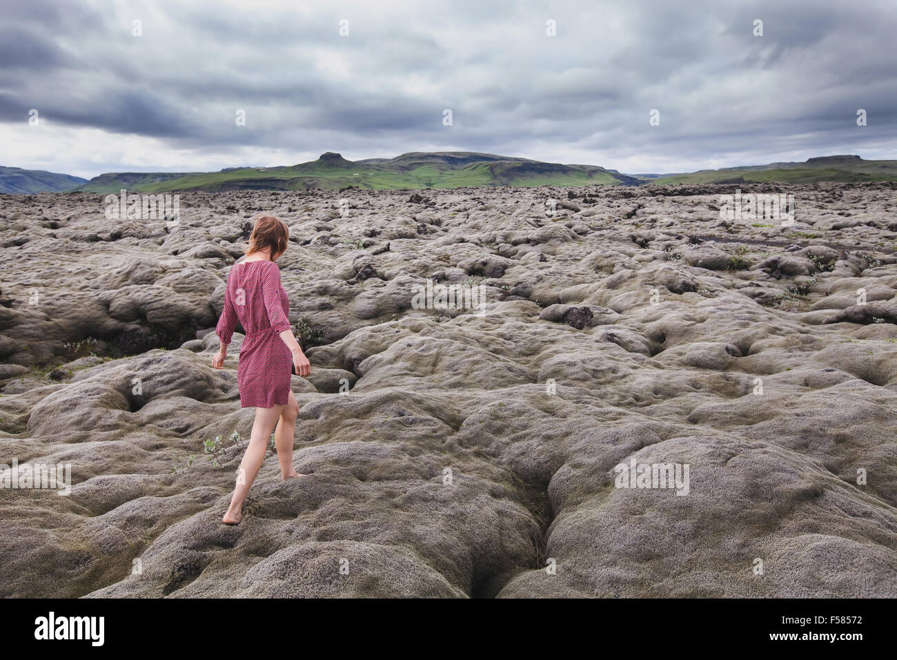fashion woman walking barefoot in lava field in Iceland - Stock Image