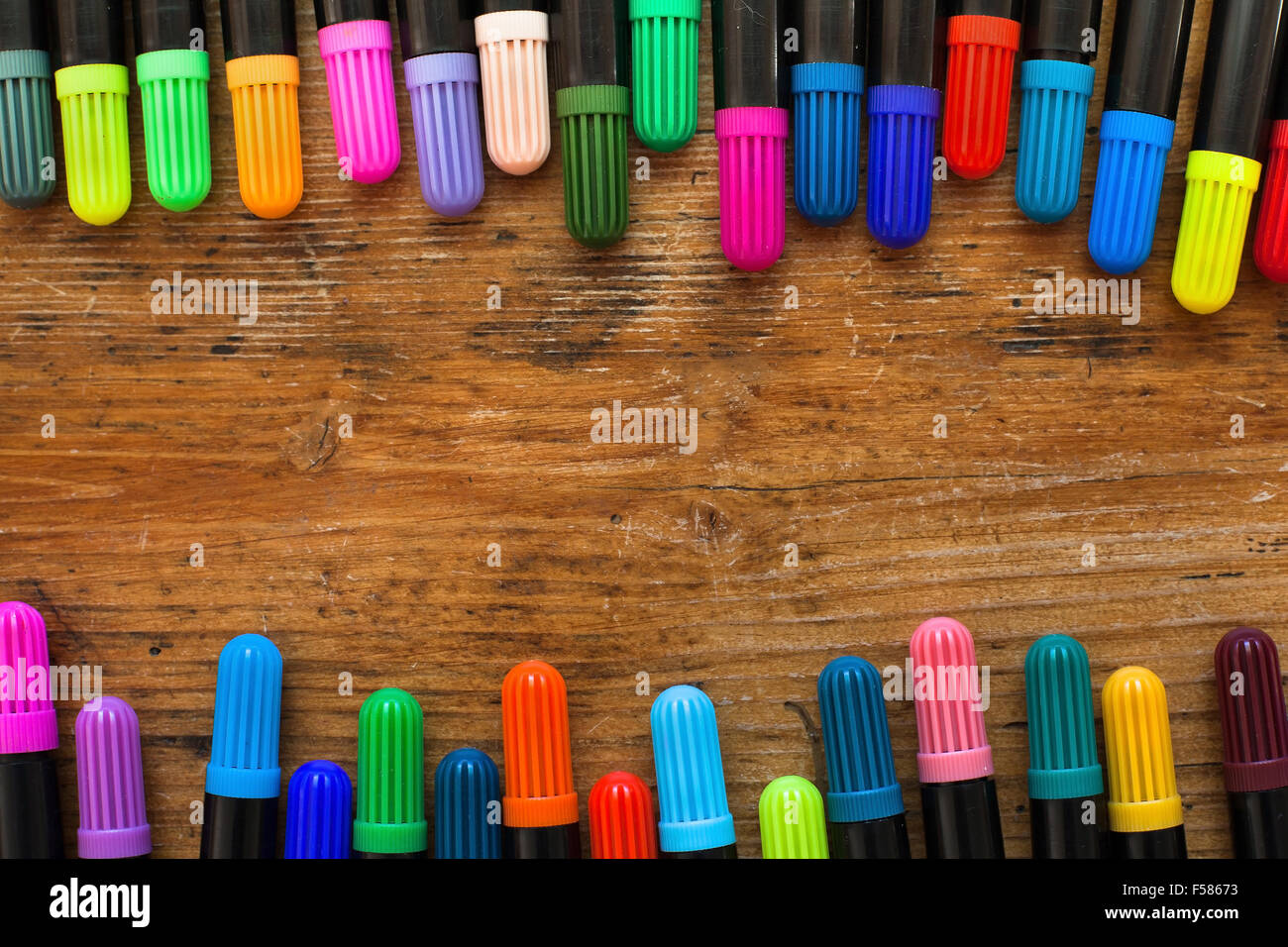 colorful markers on wooden desk, background - Stock Image