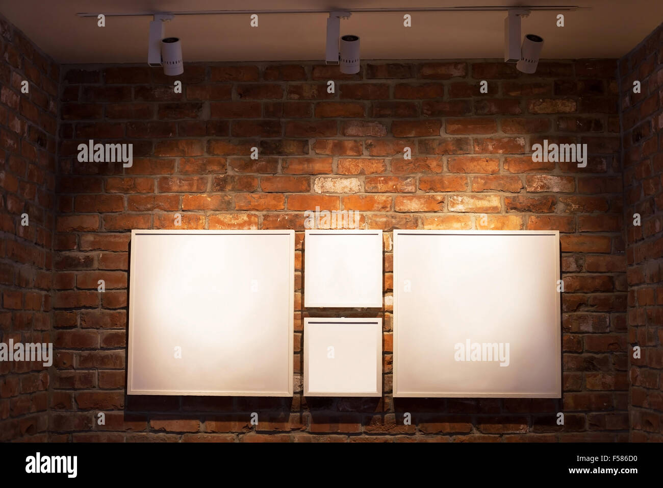 blank white boards in frames on brick wall, abstract interior background with place for text - Stock Image