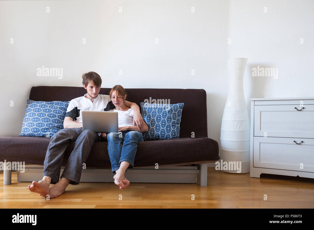 young family using laptop at home, couple on the couch with computer Stock Photo