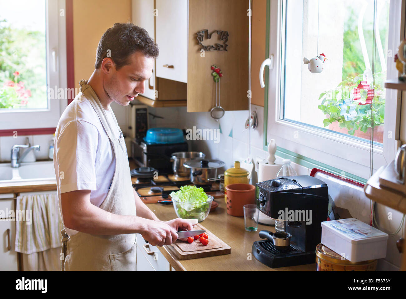 cooking healthy food, young male cutting tomatoes in the kitchen - Stock Image