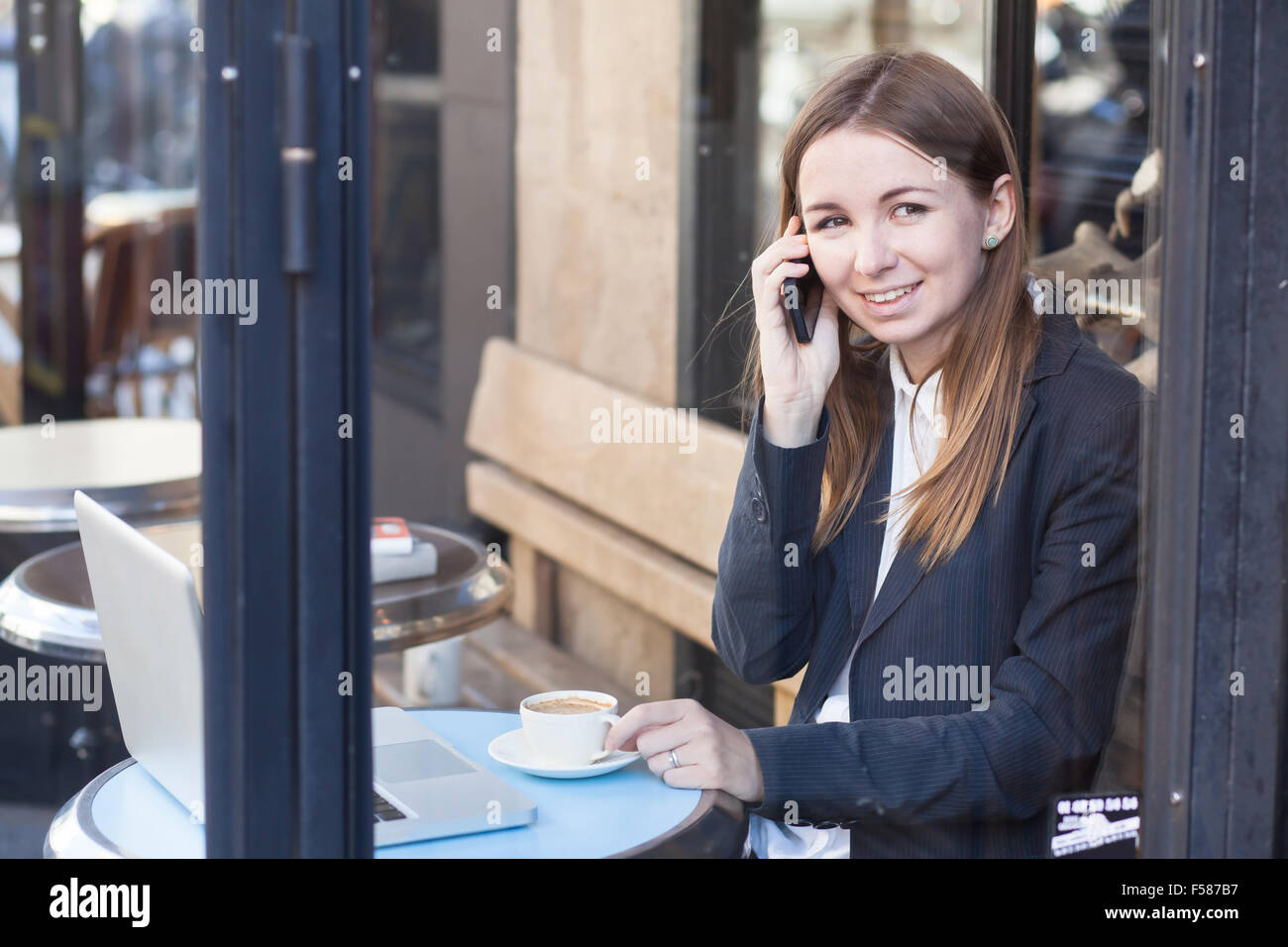 smiling business woman talking by phone in cafe - Stock Image
