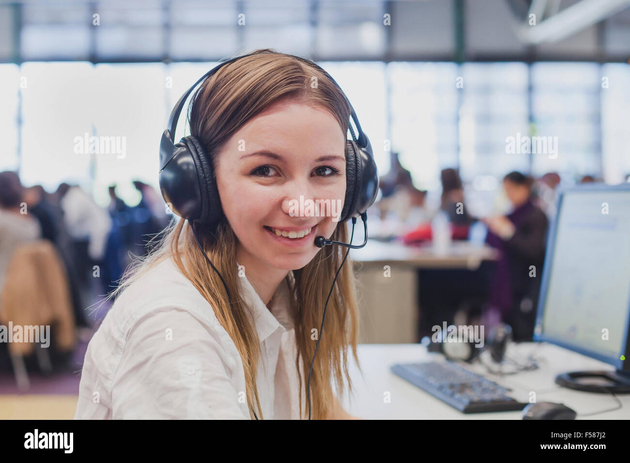 happy student with headphones and computer in university - Stock Image