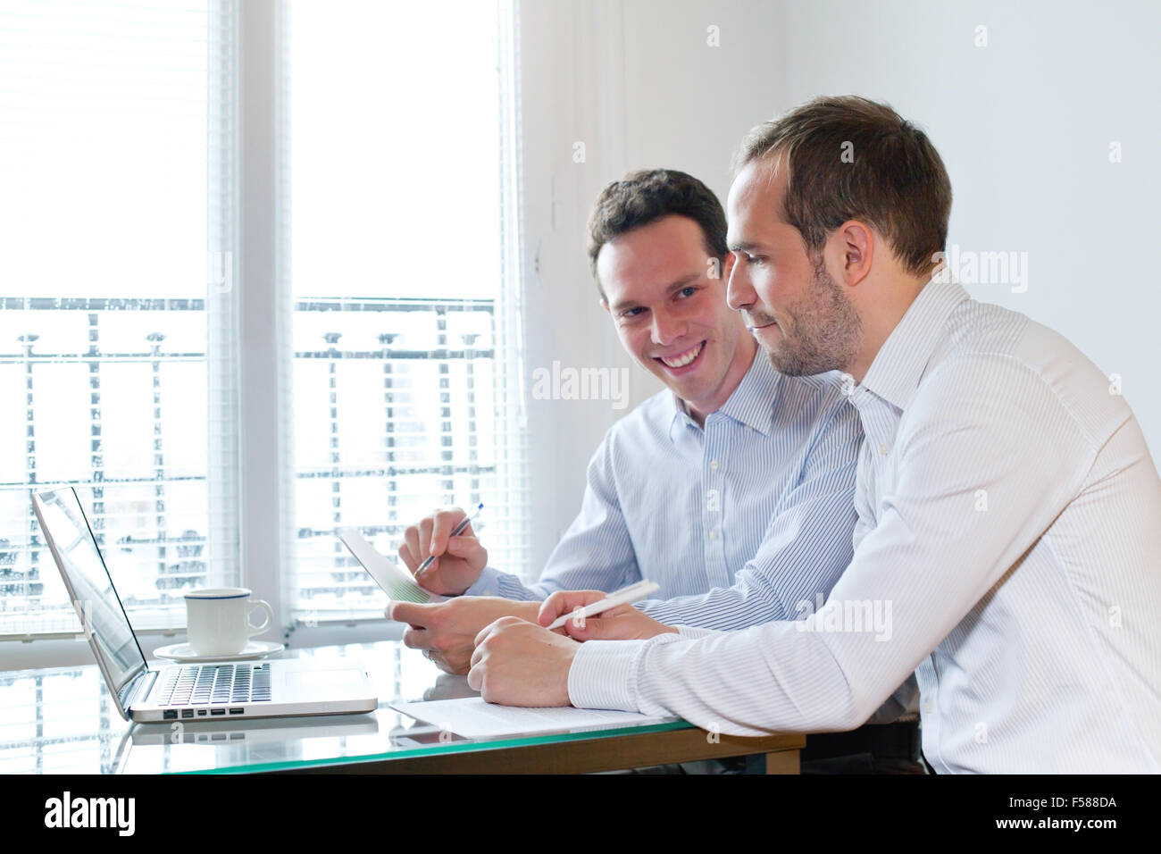 two smiling happy business men working on project in the office - Stock Image