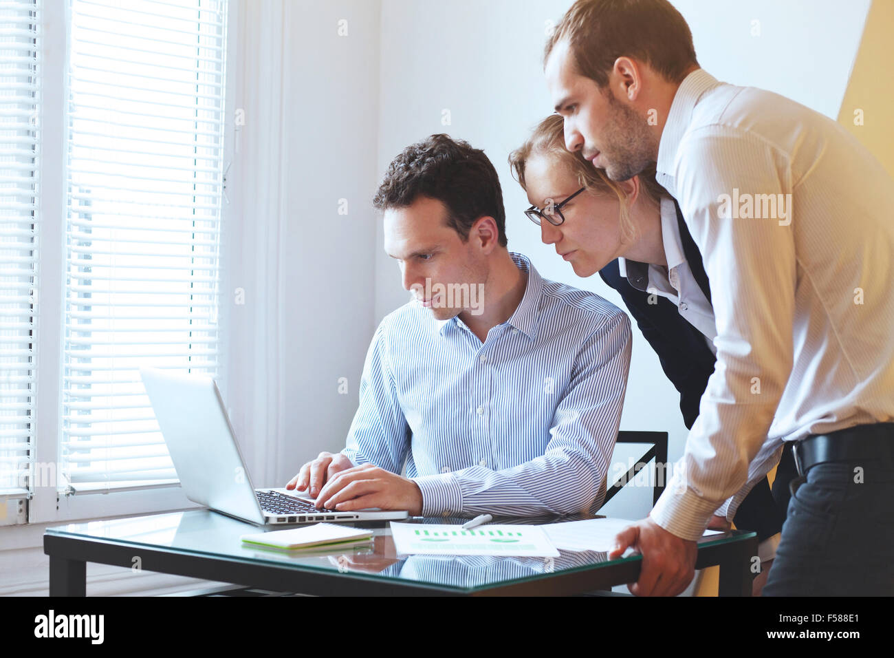 group of young business people looking at the screen of computer - Stock Image