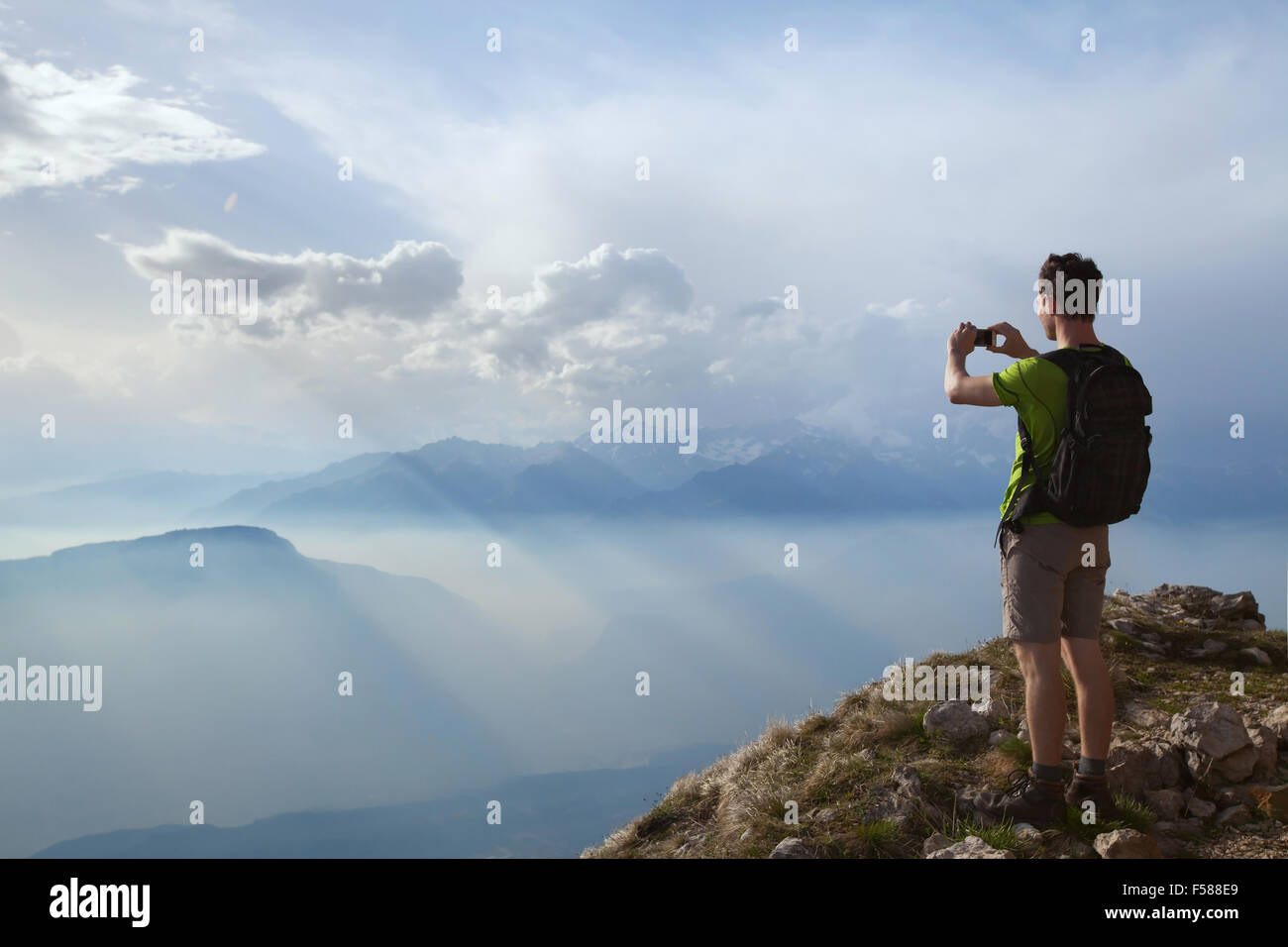 hiker taking photo of beautiful mountain landscape with mobile phone - Stock Image
