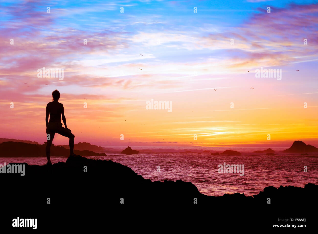 wellbeing concept, silhouette of person enjoying beautiful sunset with view of ocean - Stock Image