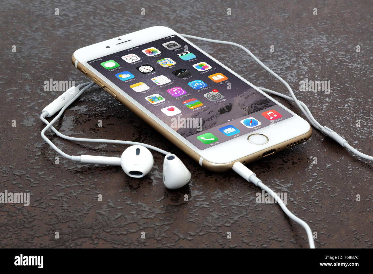 Golden iPhone 6 on stone table - Stock Image