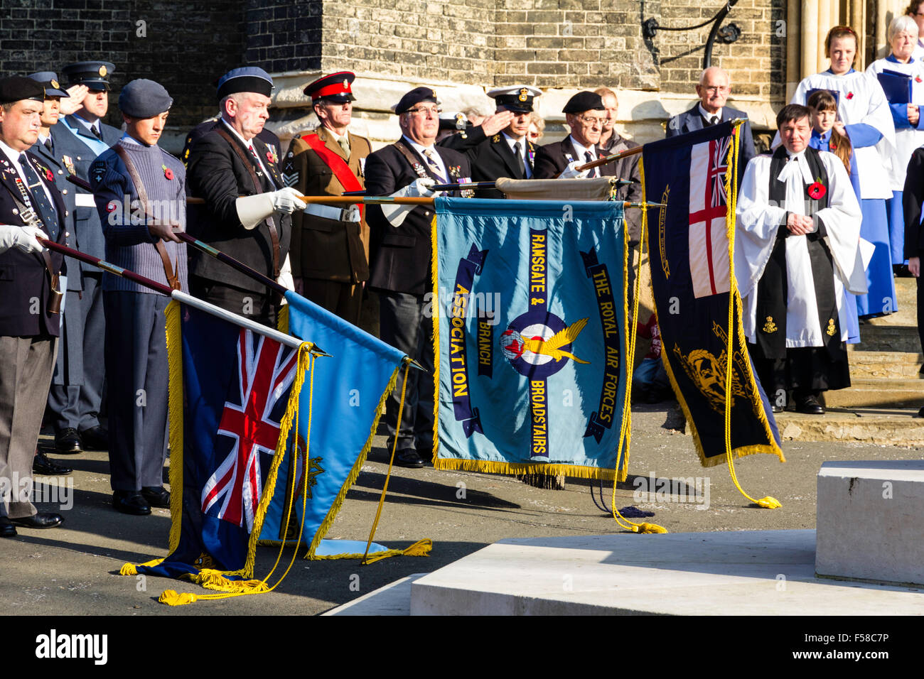 England, Ramsgate. Remembrance Sunday. Ex-servicemen, soldiers standing at attention in a line, while lowering flags - Stock Image