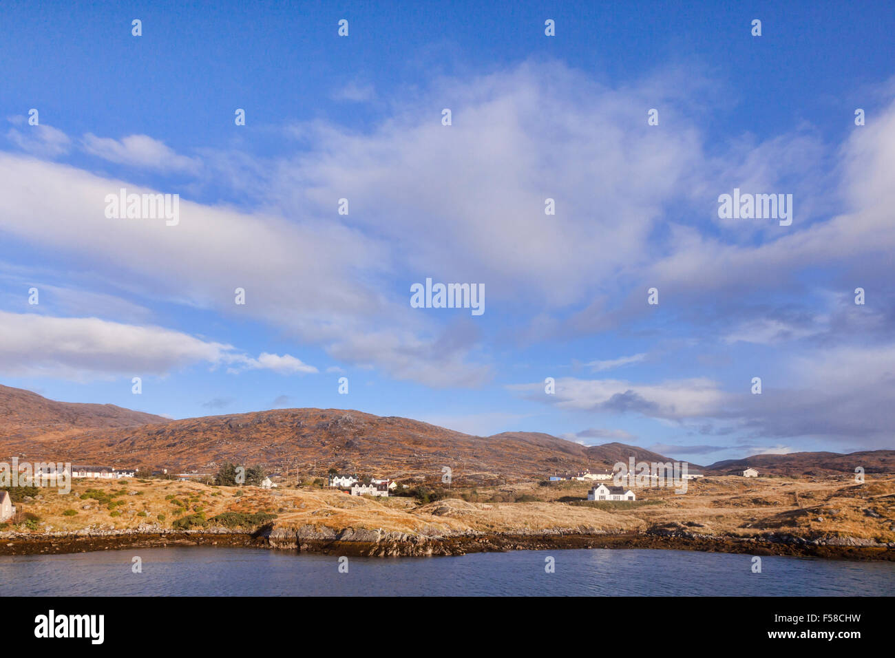 Houses along the shore approaching the port of Tarbert on the Isle of Harris, Outer Hebrides,Scotland,UK. Stock Photo