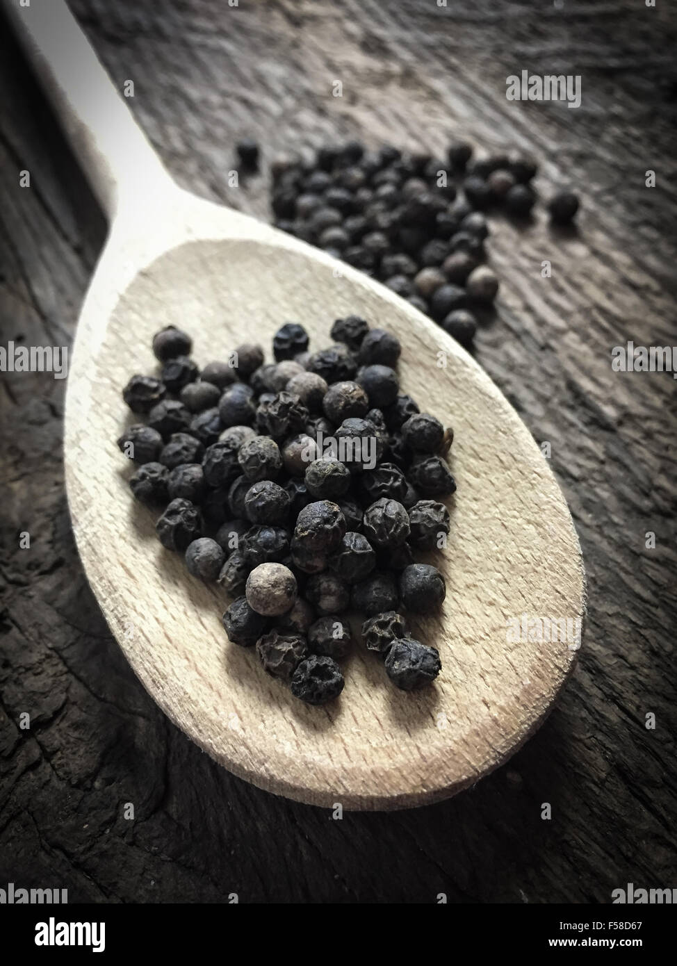 Fine served black peppercorns on wooden background - Stock Image