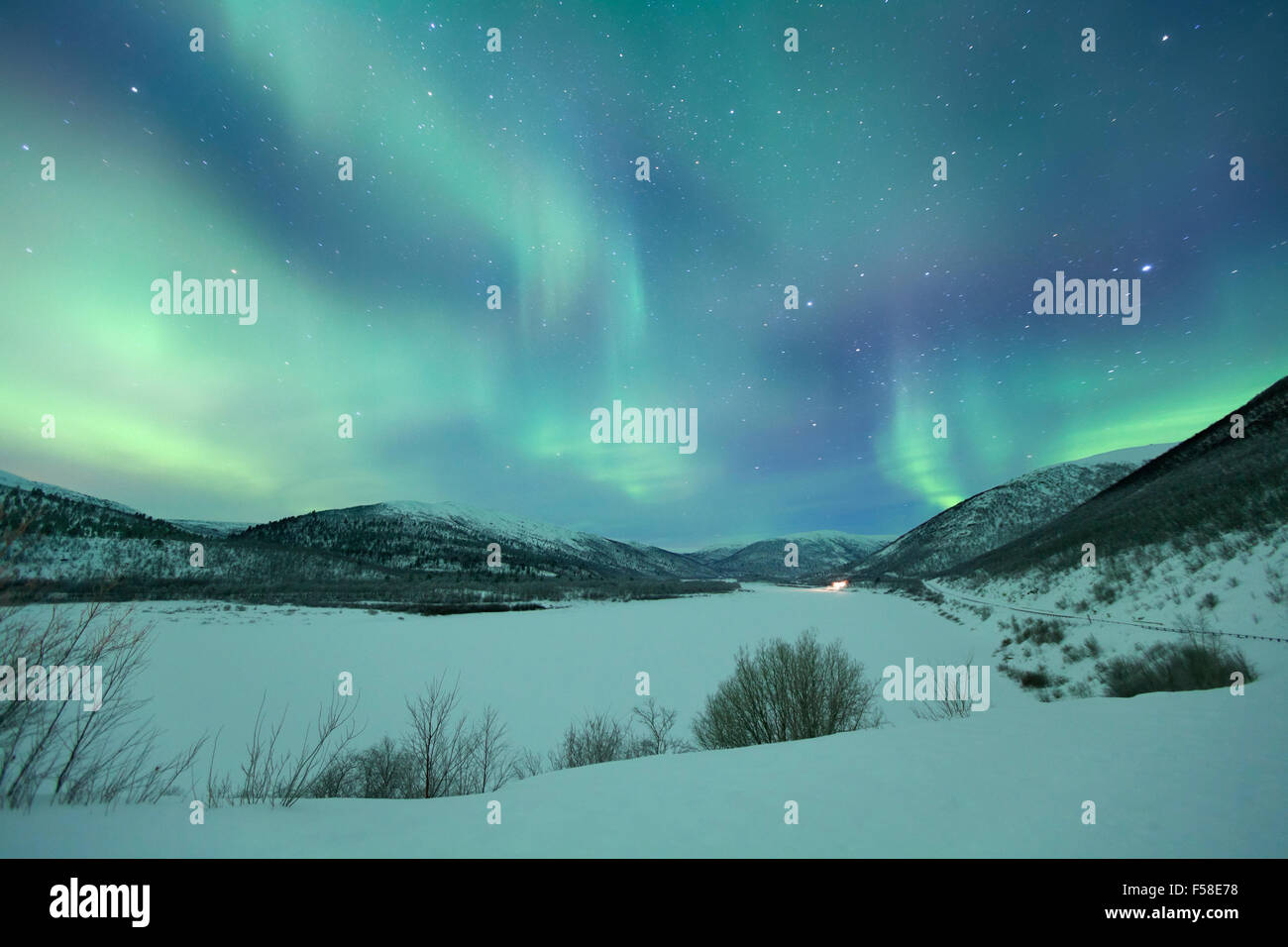 Spectacular aurora borealis (northern lights) over a snowy winter landscape in Finnish Lapland. - Stock Image