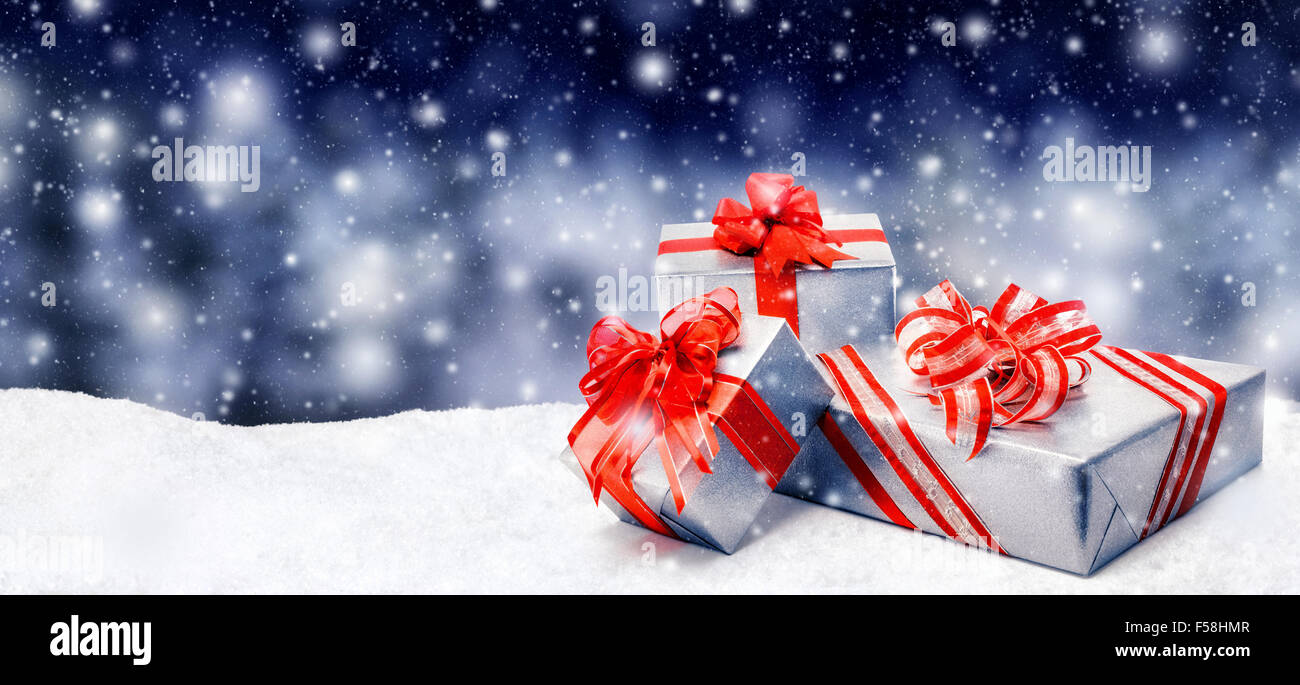 Silver Christmas or birthday gift boxes with red bows in snow, with snowy night background, panorama format - Stock Image
