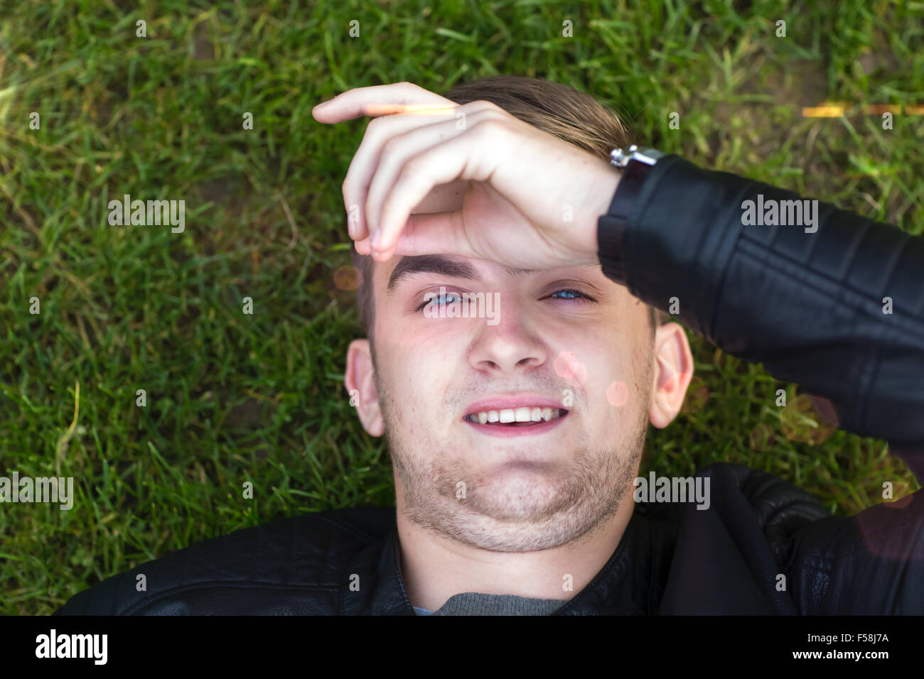 Young man lying on the grass looking at the camera. Close up. Stock Photo
