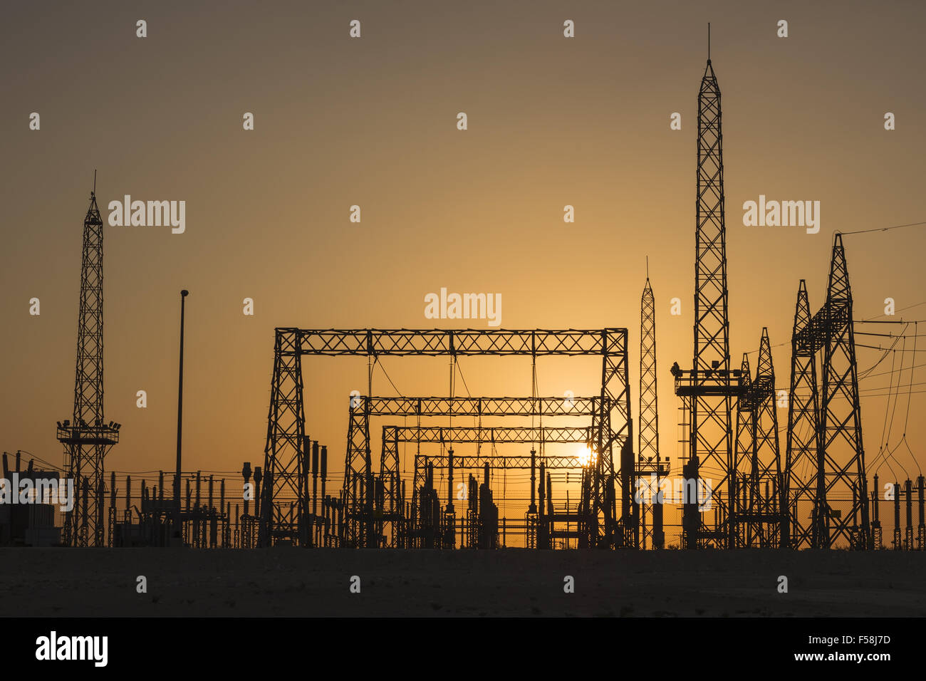 A sunrise photo through sand in the air. Photo of a power sub-station in Bahrain, Middle East. - Stock Image
