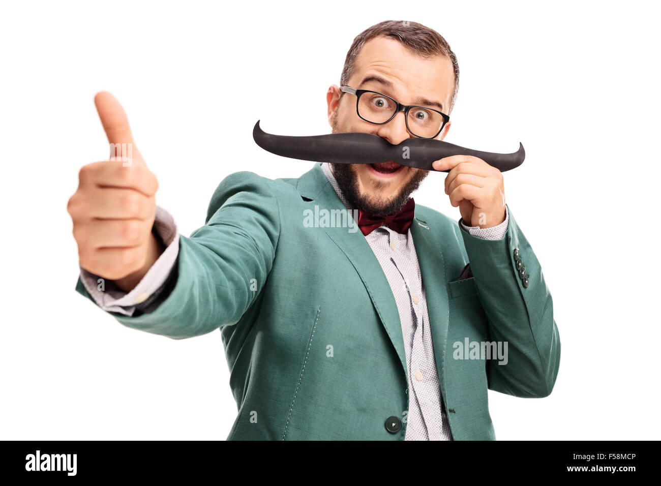 Excited young man holding fake moustache on his face and giving a thumb up isolated on white background - Stock Image
