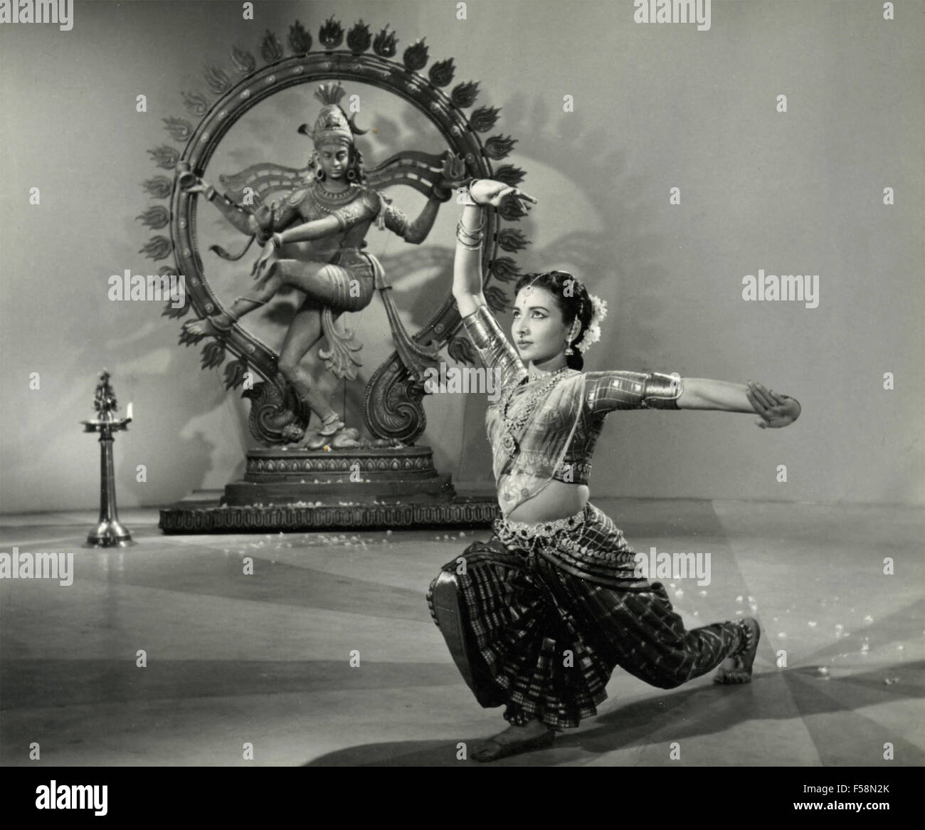 An Indian woman dancing next to the statue of Shiva Nataraja - Stock Image