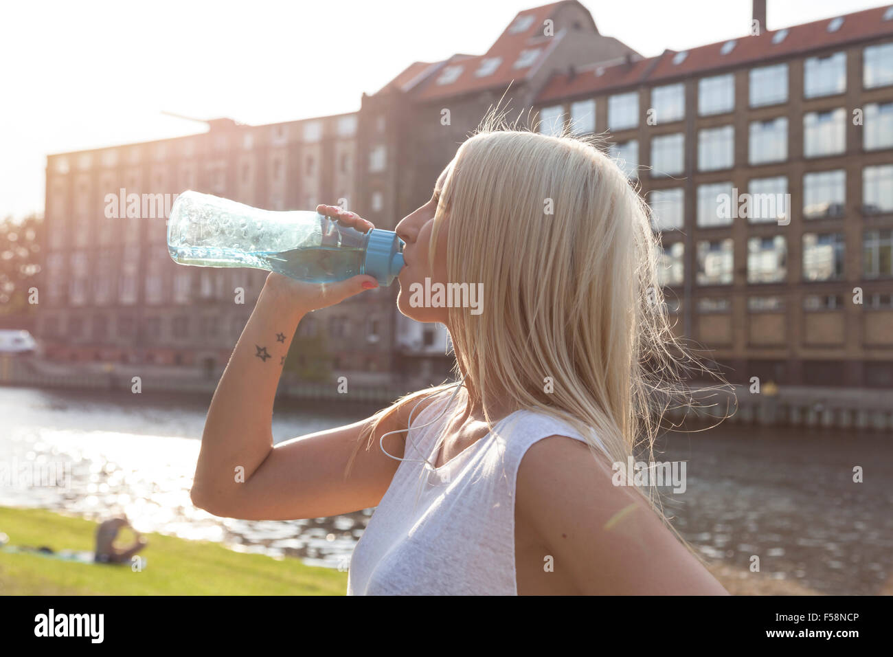 Woman drinking from a botte in summer in Berlin - Stock Image