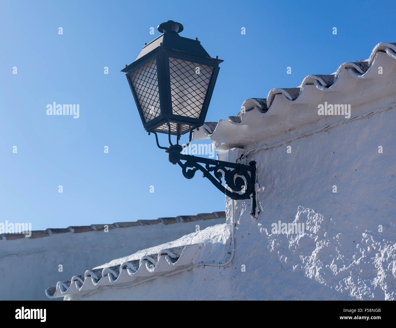 Ornate street lamp in a whitewashed courtyard in Campo de Criptana in Castilla-La Mancha, Spain - Stock Image