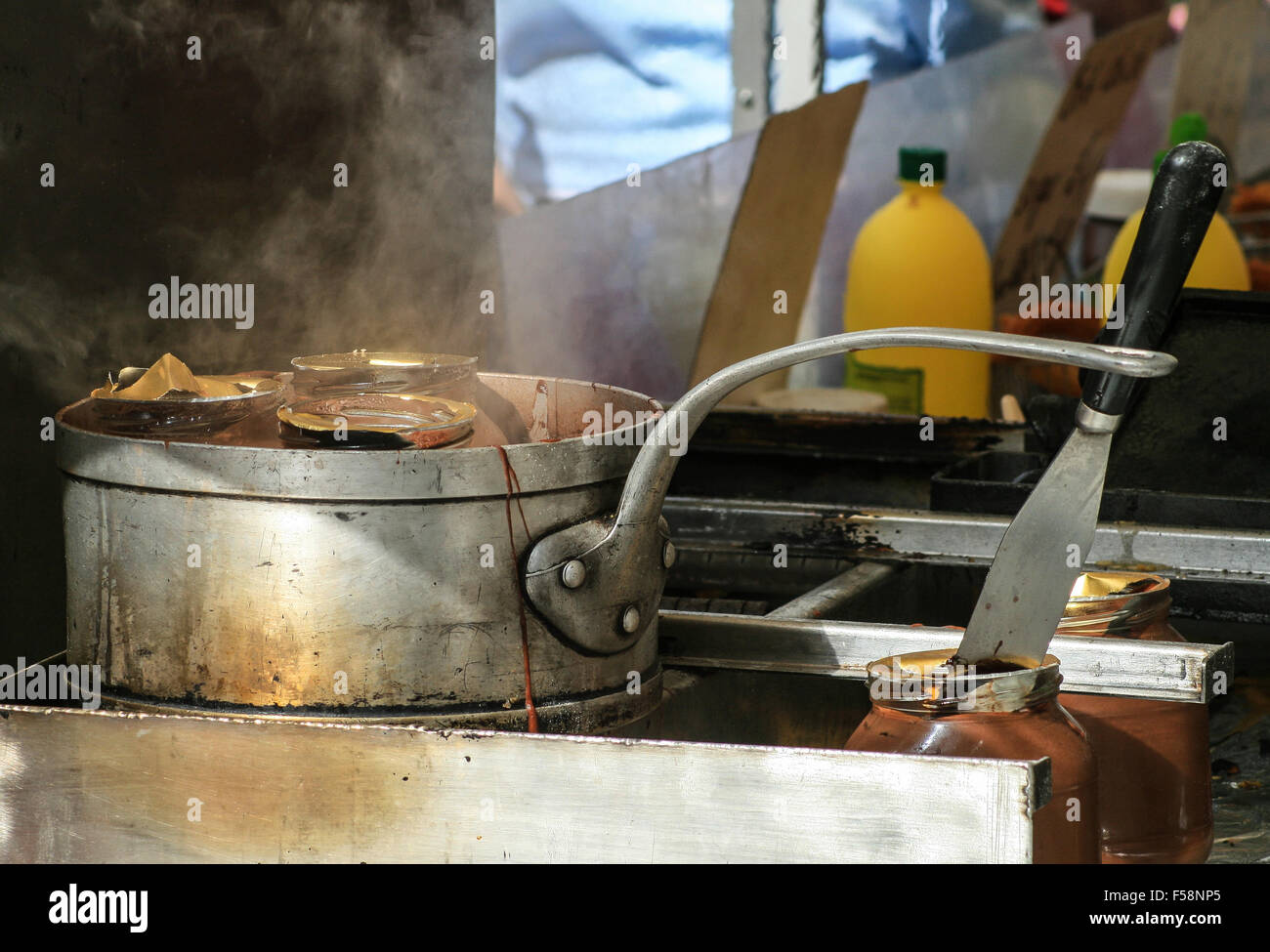 A basic cooking set up in a mobile kitchen with a pan of hot food simmering on a cooker Stock Photo