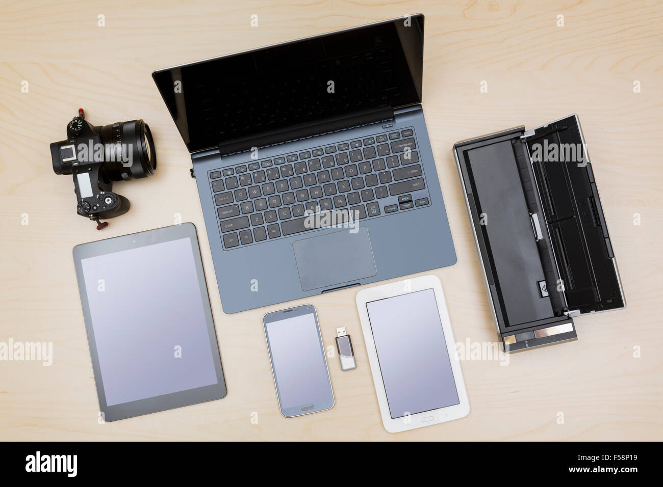 Overhead view of digital equipment, devices or gadgets - laptop, notebook, camera, tablet, phone, scanner on a desk - Stock Image