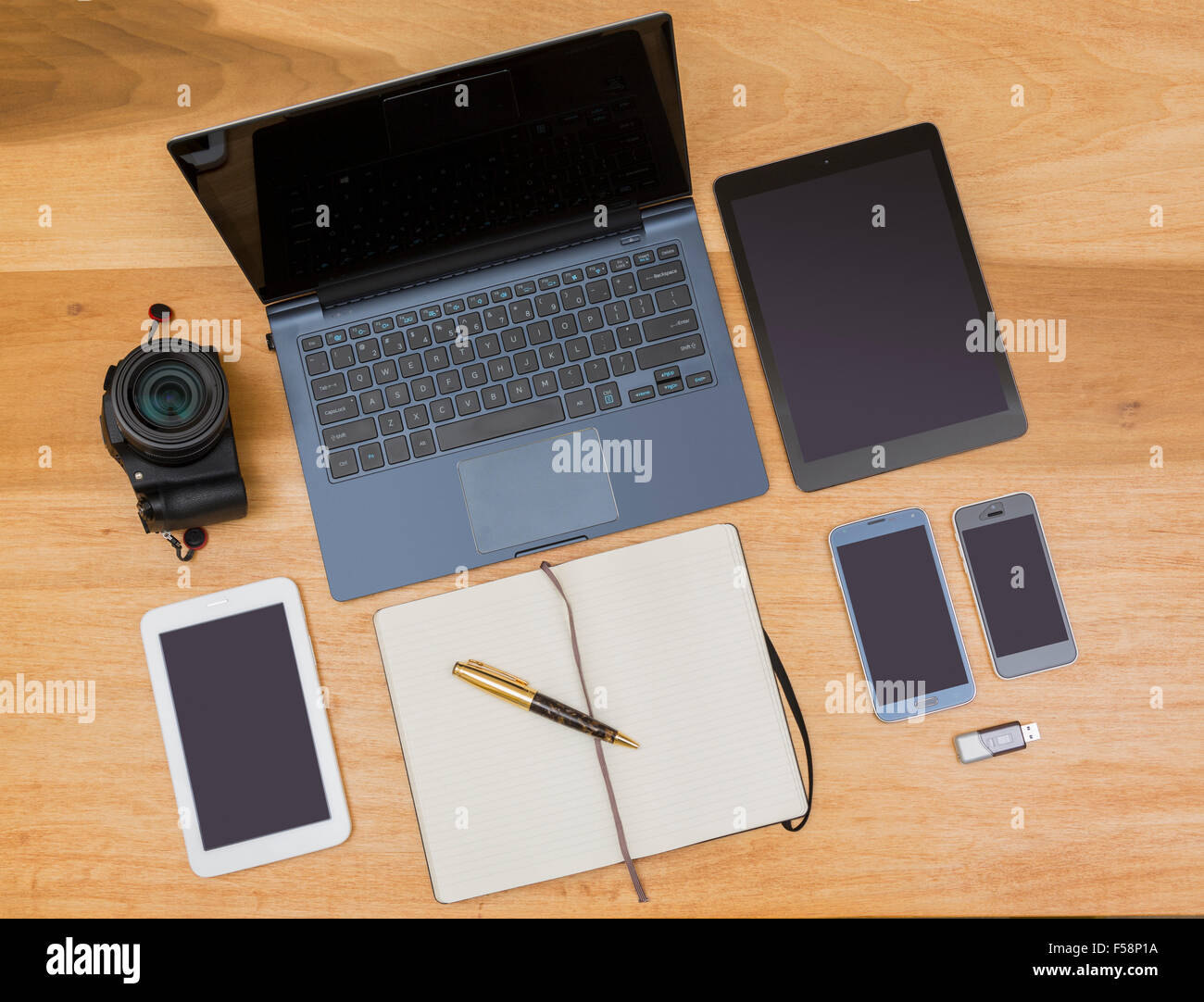 Overhead view of desk with laptop, smartphones, tablets, camera and notebook and pen - digital design / evolution - Stock Image