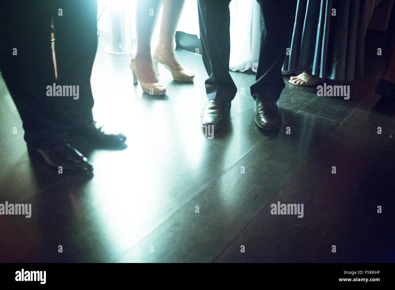 Legs of young lady wearing high heels shoes and men in suits ...