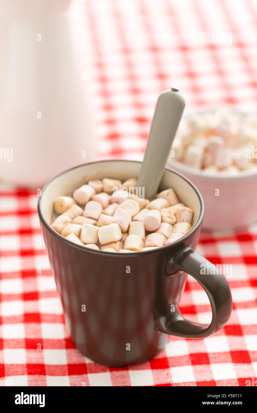 Cocoa drink with marshmallows in mug on checkered tablecloth - Stock Image