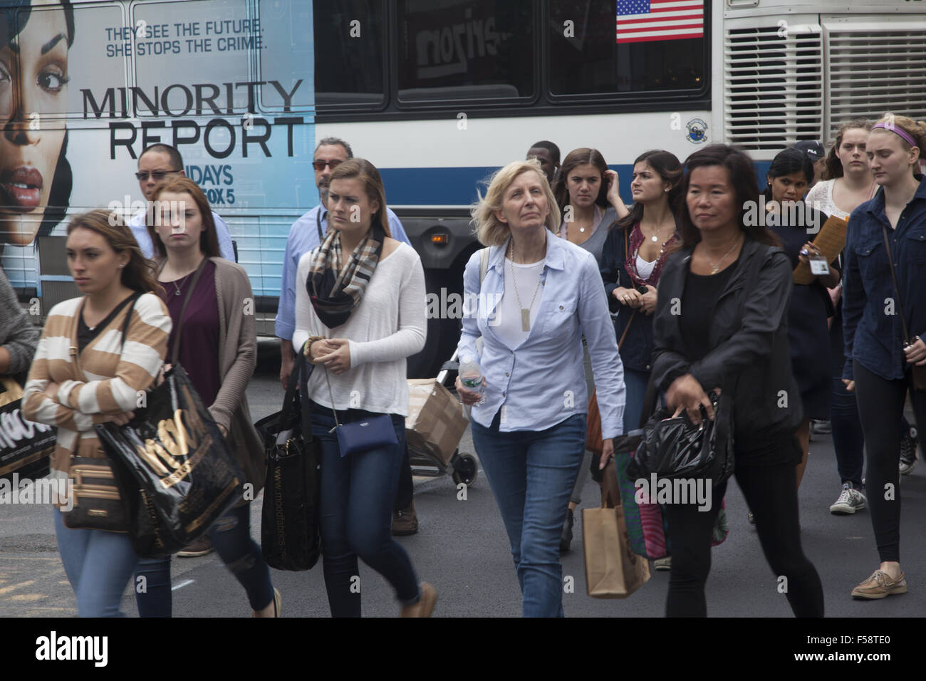 Pedestrians cross 6th Avenue along 42nd Street in midtown Manhattan. - Stock Image