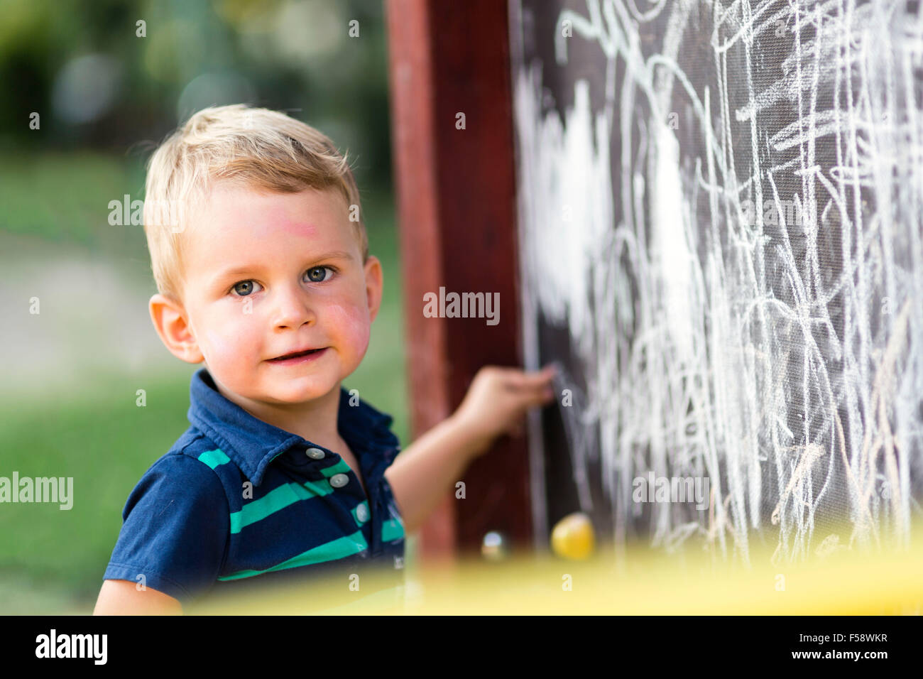 Creative cute toddler drawing with chalk outdoors - Stock Image