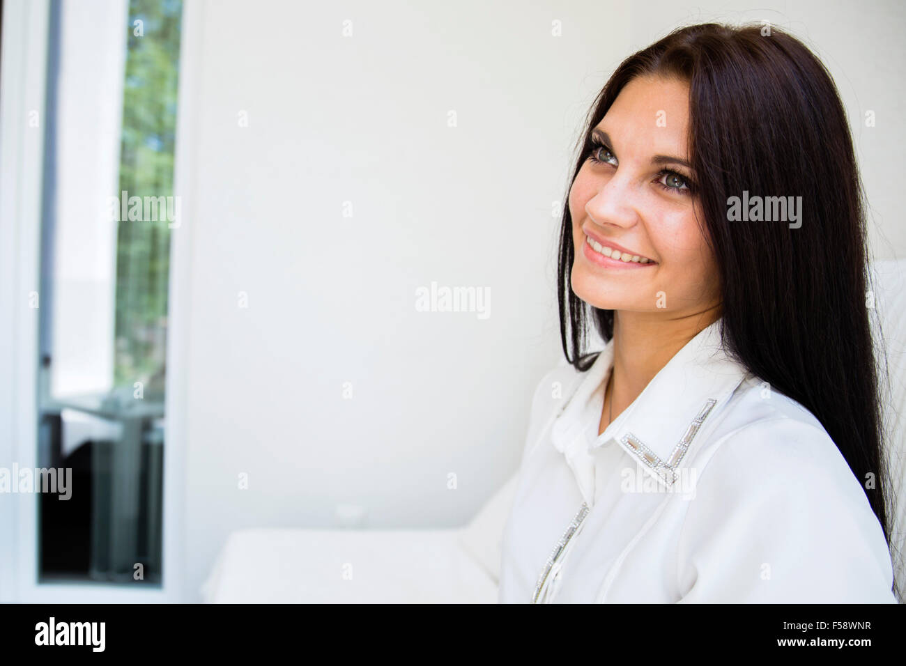 Portrait of a white beautiful woman smiling outdoors - Stock Image