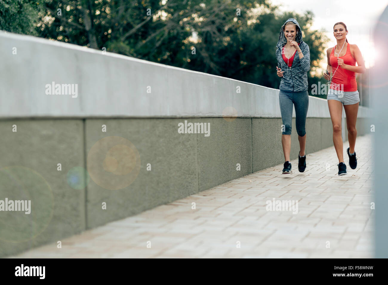 Active female joggers running outdoors and listening to music - Stock Image