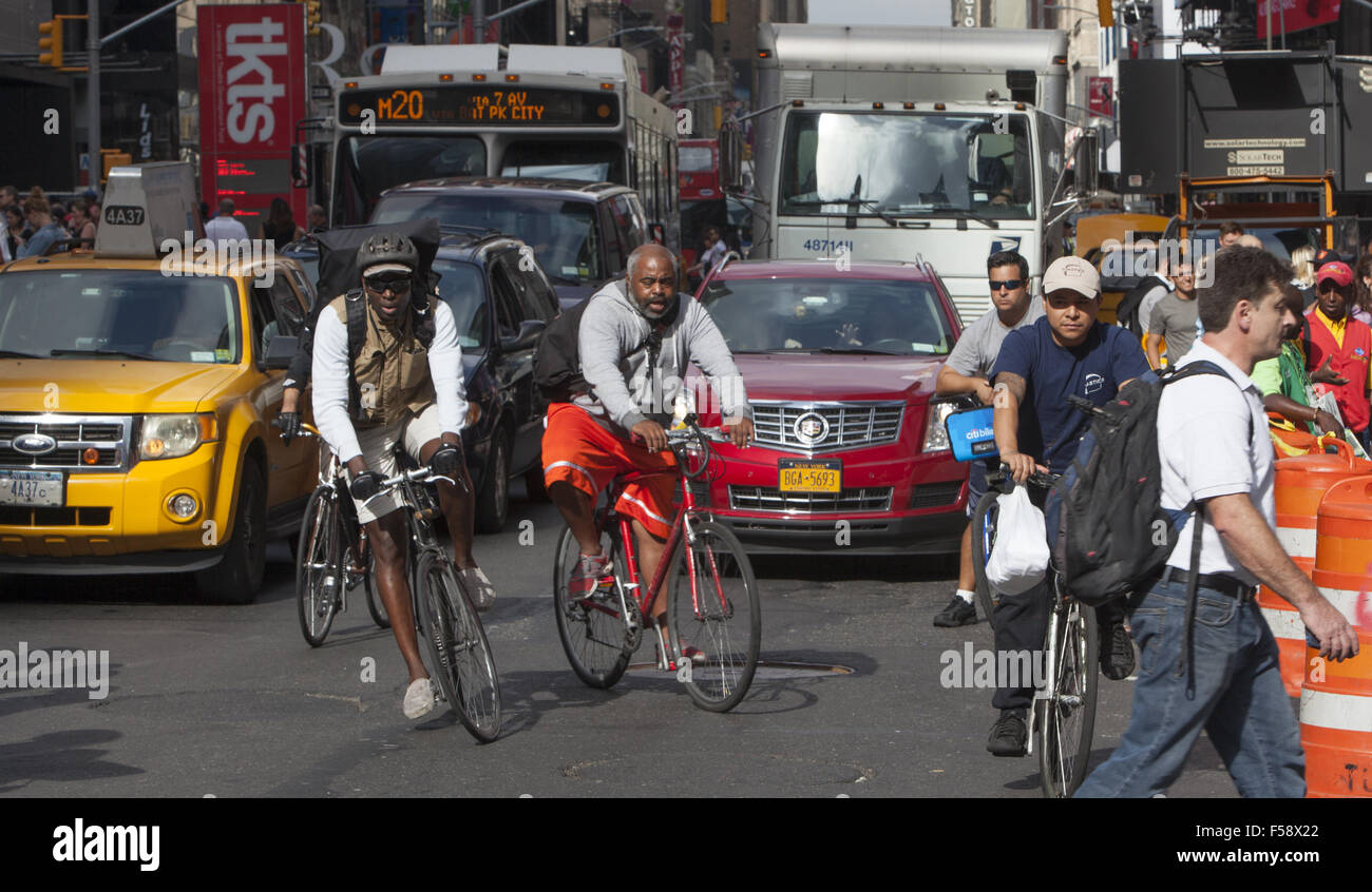 Brave bike messengers ride bikes amidst the constant din of traffic on 7th Avenue in Times Square, NYC. - Stock Image