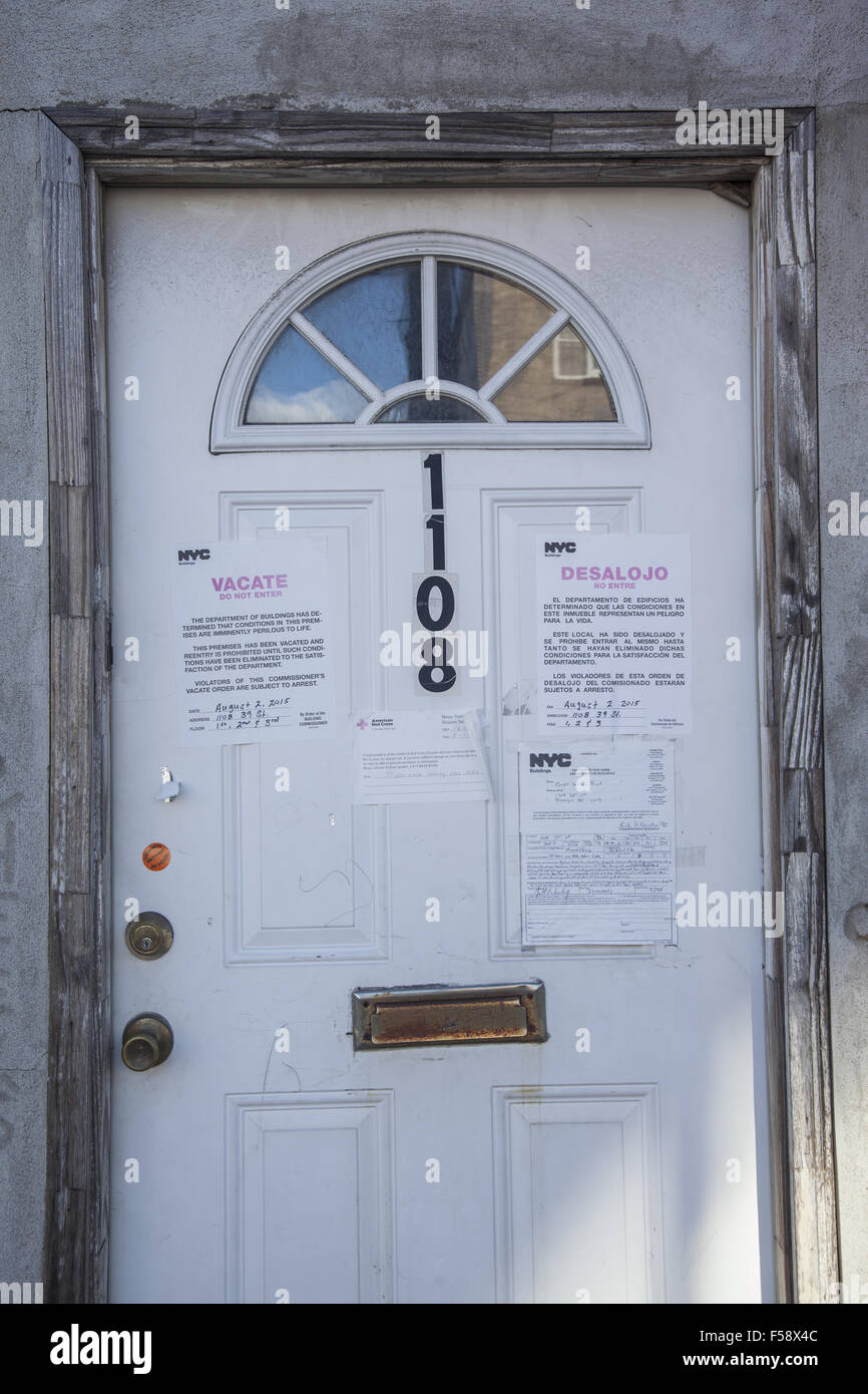 Front door of a condemned building with a 'Vacate Premises' sign on the front door in Brooklyn, NY. - Stock Image