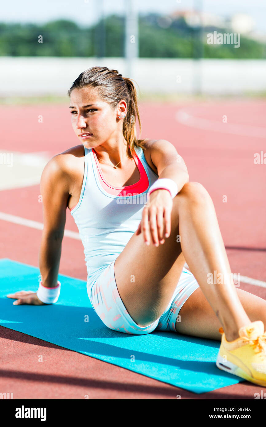 Young fit woman stretching outdoors on a sunny day - Stock Image