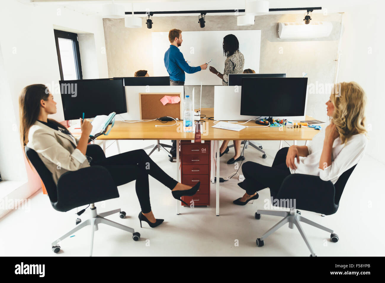 Young business people sitting in office while listening to the lecturer and learning new technologies displayed - Stock Image