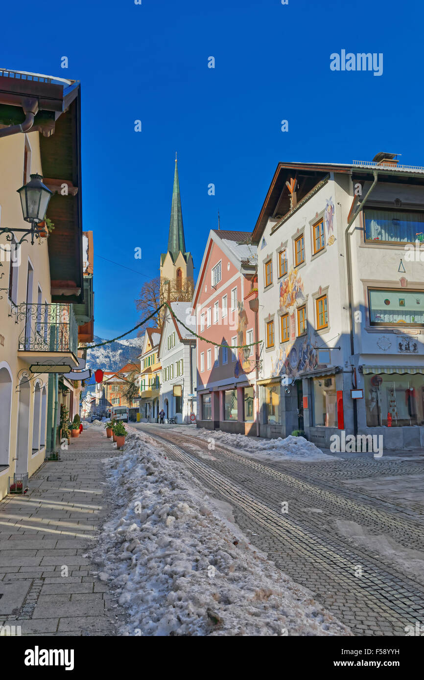 Cozy street with lovingly painted houses and Maria-Himmelfahrt (Assumption day) church in Garmisch-Partenkirchen. - Stock Image