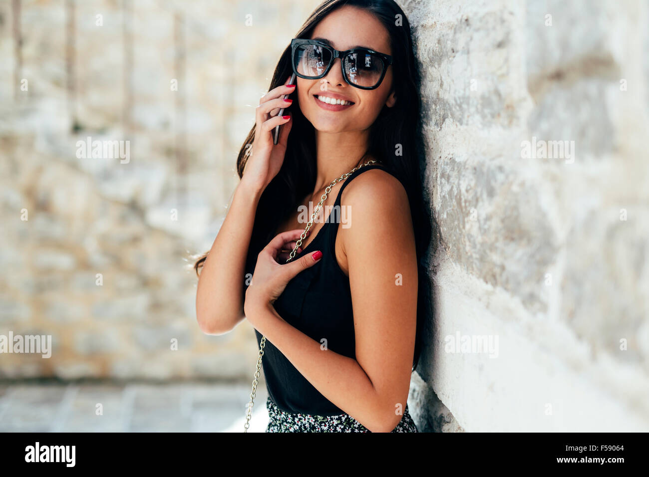 Beautiful fashion model using phone in summer outdoor - Stock Image