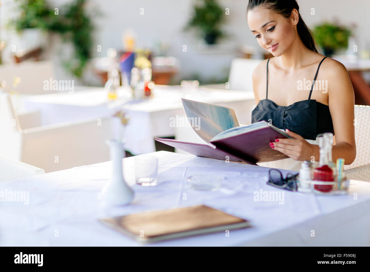 Beautiful woman ordering from menu in restaurant and deciding what to eat - Stock Image