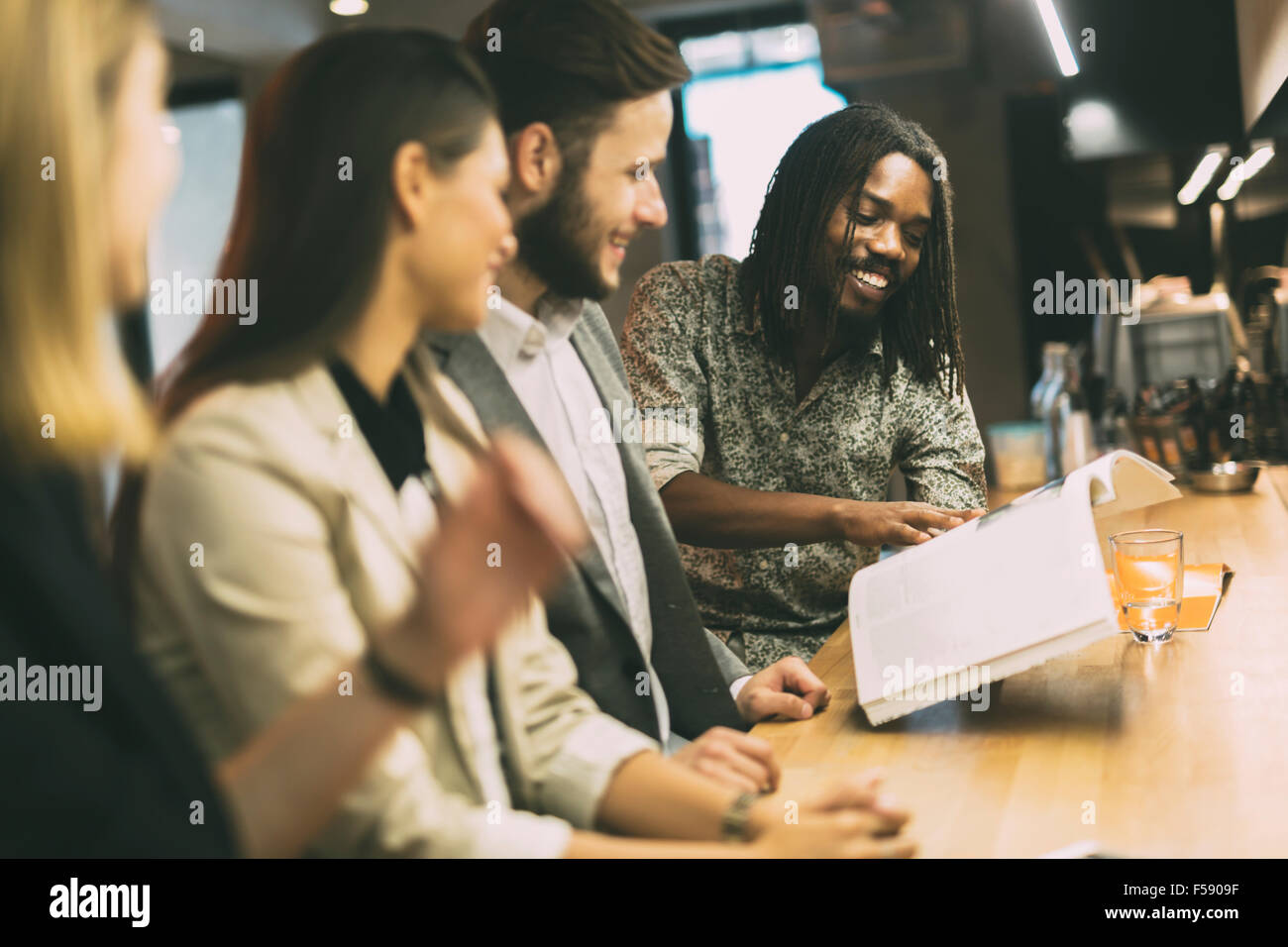 Group of people discussing the contents of the article while sitting in a bar - Stock Image