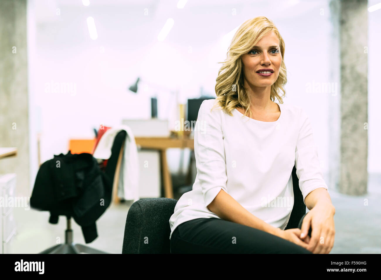 Beautiful blonde businesswoman sitting in an office with legs crossed - Stock Image