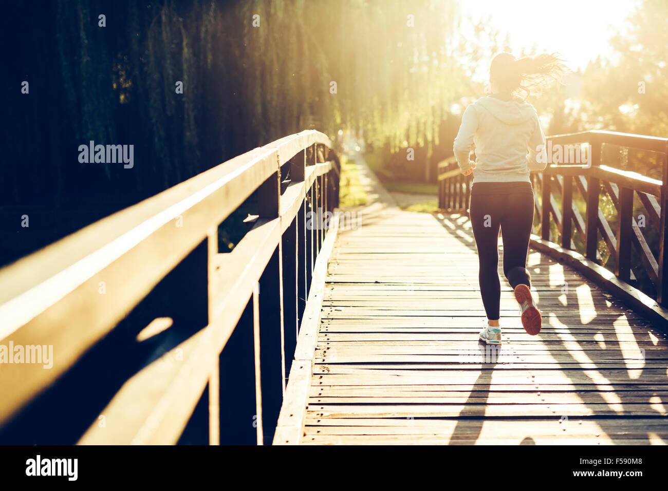 Beautiful female jogger running during sunset across bridge - Stock Image