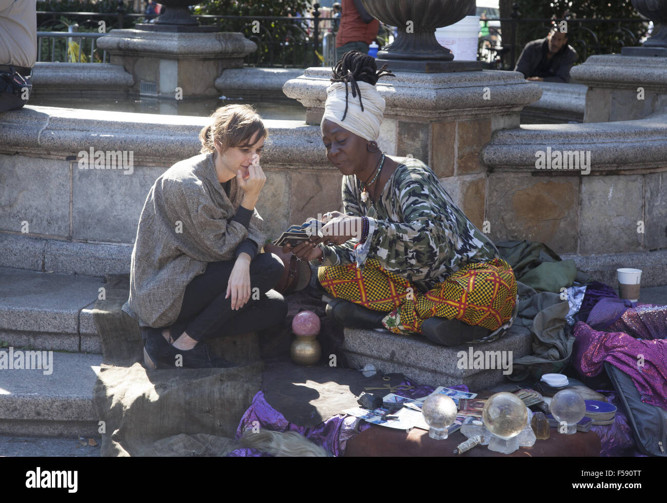 fortune teller gives a woman a Tarot card reading at Union Square in Manhattan, NYC. - Stock Image