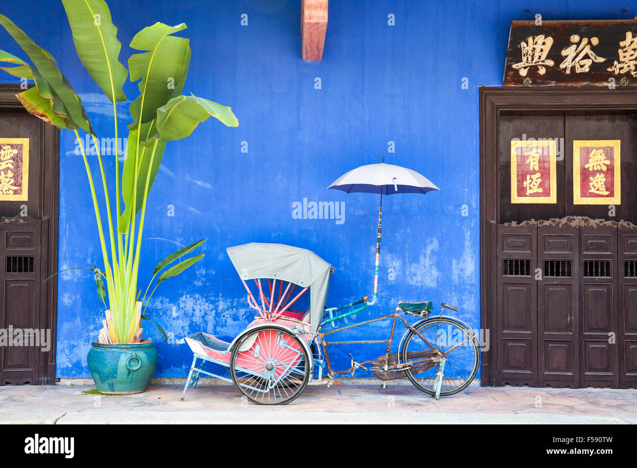 Georgetown, Malaysia — 04 August, 2014: Old rickshaw tricycle near Fatt Tze Mansion or Blue Mansion, famous oriental Stock Photo