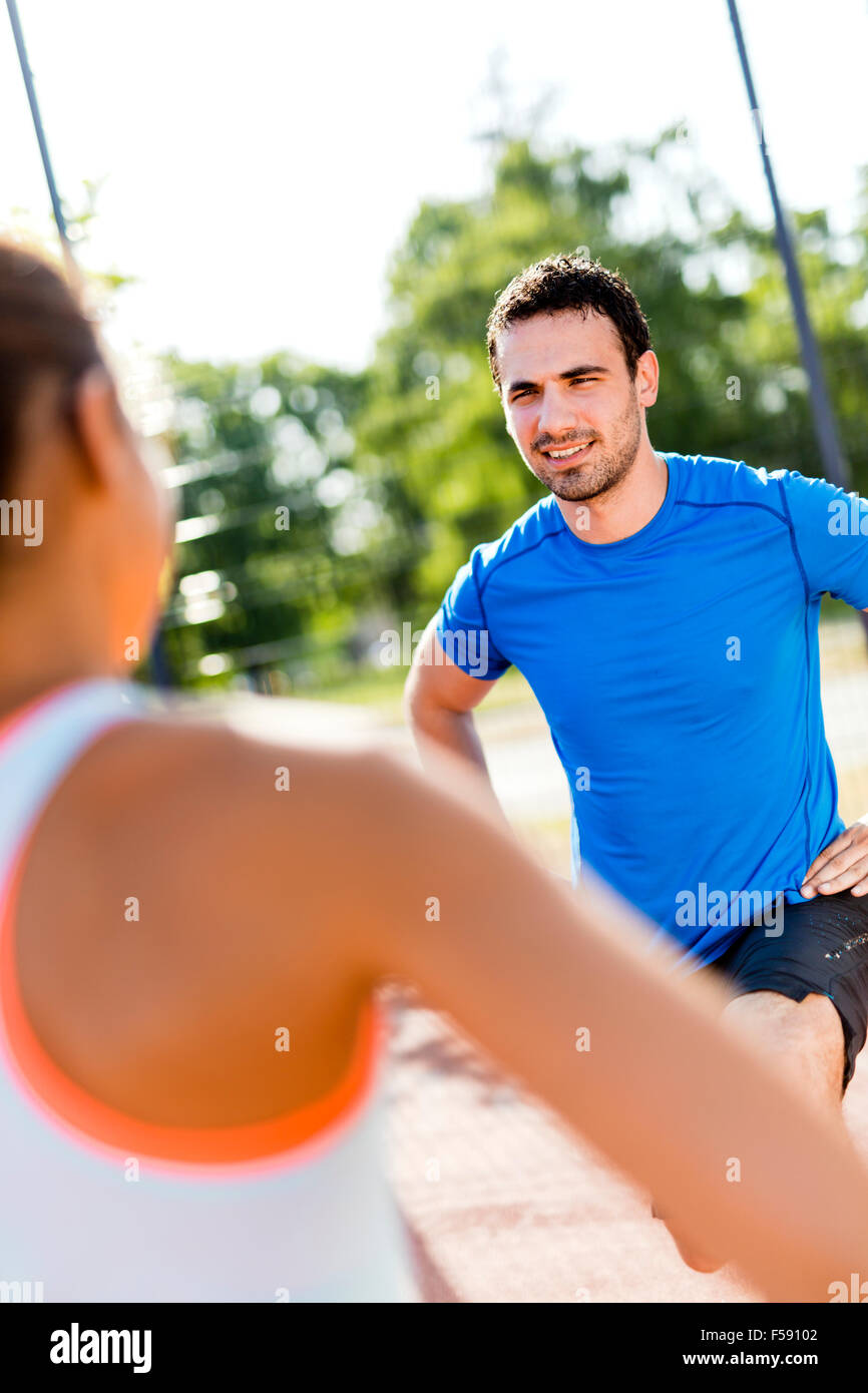 Young athletic man and woman stretching outdoors on a hot summer day facing each other Stock Photo