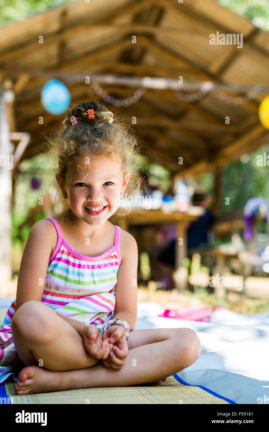 Beautiful curly haired young girl smiling outdoors - Stock Image