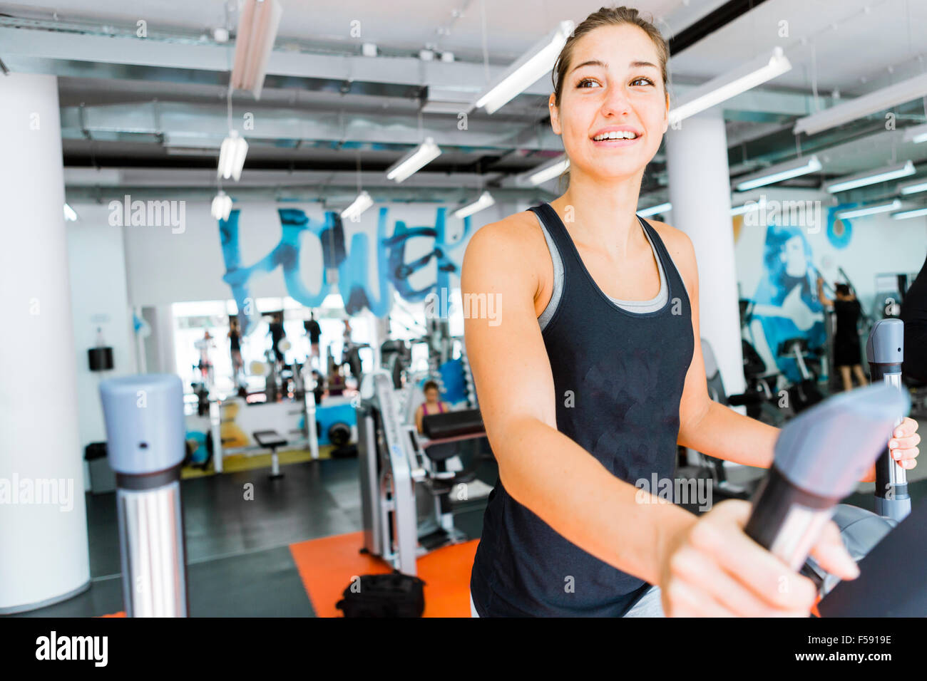 Young fit woman using an elliptic trainer in a fitness center and smiling Stock Photo