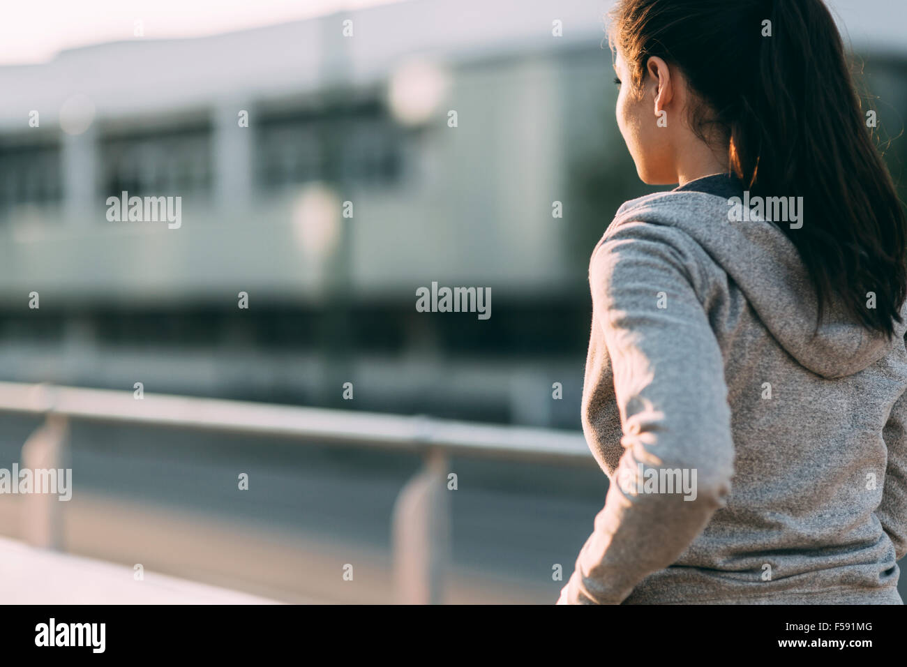 Woman jogging in city and keeping her body in shape - Stock Image