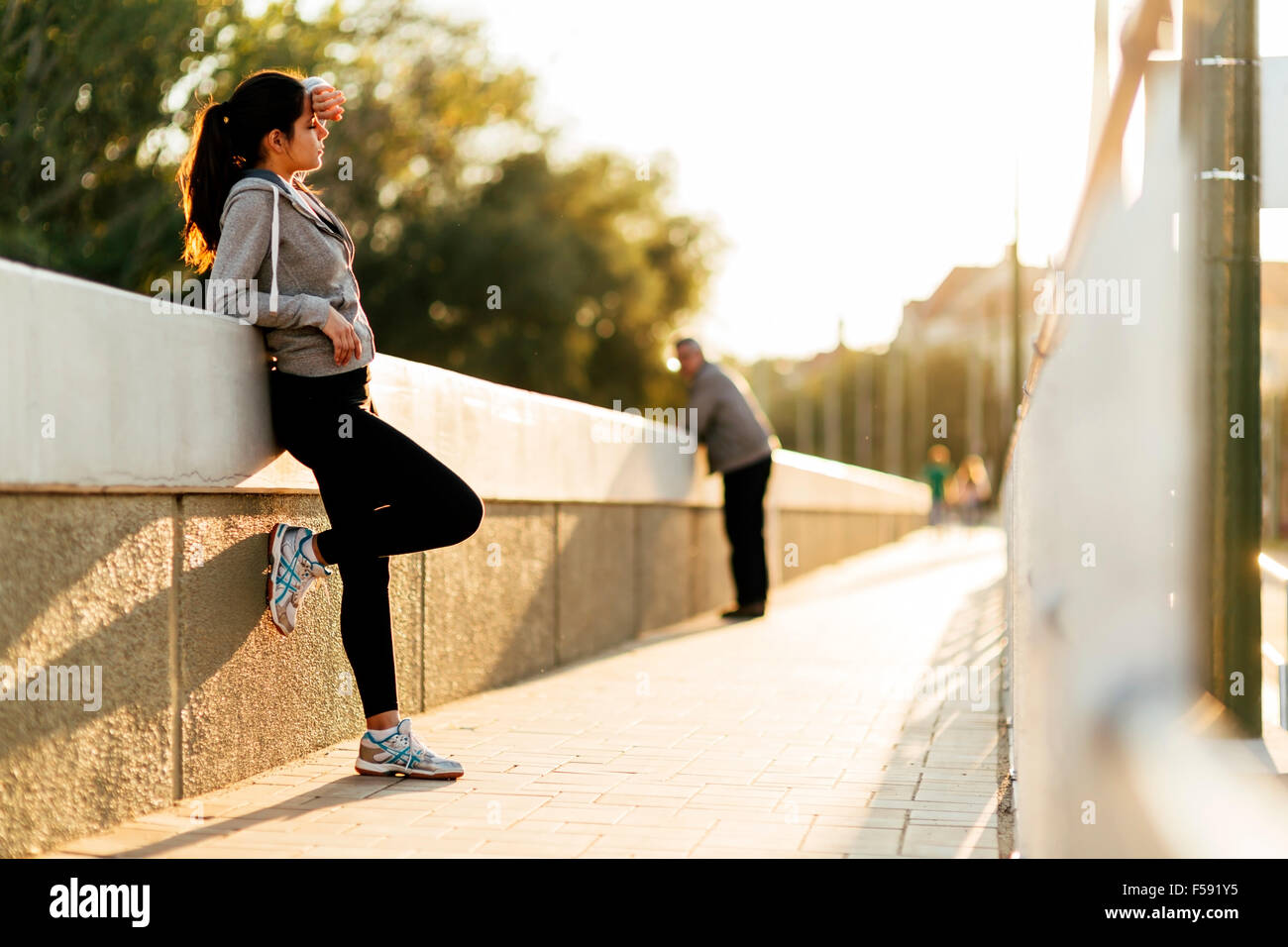 Beautiful woman resting after jogging in city - Stock Image