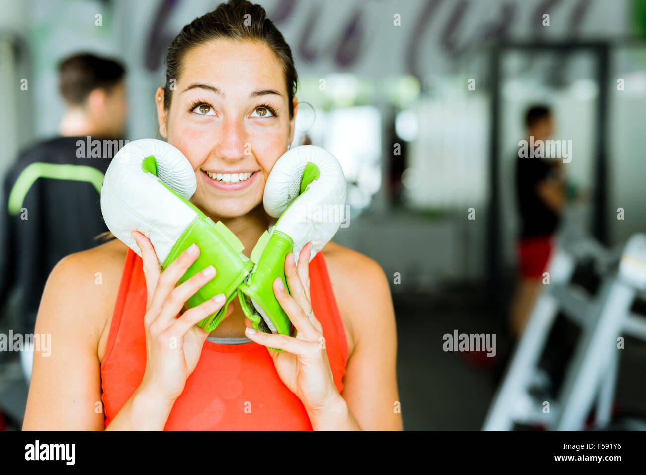 Young beautiful woman smiling and posing with boxing gloves in a gym Stock Photo